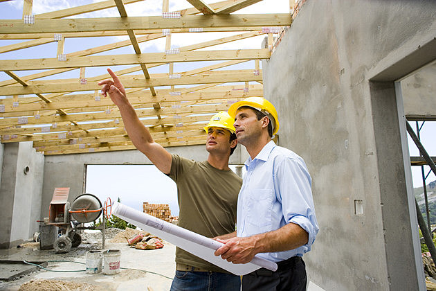 Workers with blueprints in structure